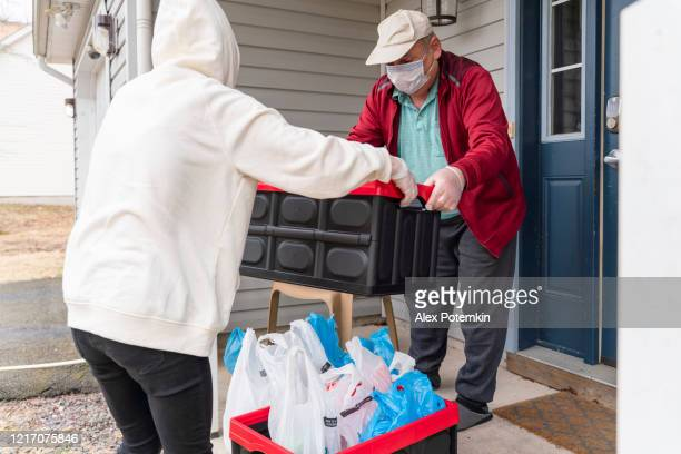 young woman wearing a protective n95 mask, a courier, is handing the groceries packed into reusable plastic bins to a customer, a senior man, on the porch of his house during covid-19 outbreak. - alex potemkin coronavirus stock pictures, royalty-free photos & images