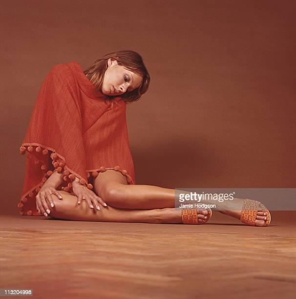 A young woman wearing a red tasselled poncho and mules circa 1970