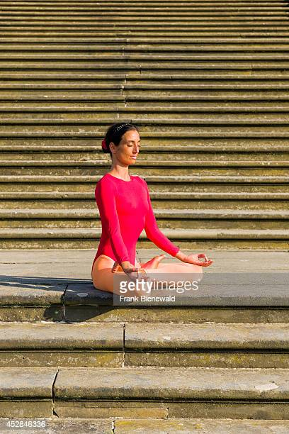 Young woman wearing a redorange body suit is practising HathaYoga outdoor showing the pose padmasana lotus pose