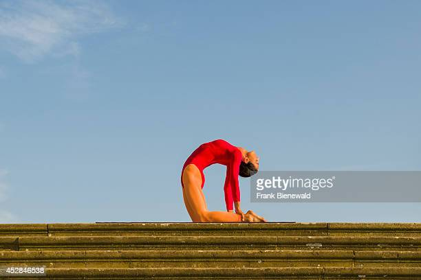 Young woman wearing a redorange body suit is practising HathaYoga outdoor showing the pose ushtrasana camel pose