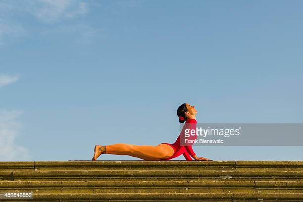 Young woman wearing a redorange body suit is practising HathaYoga outdoor showing the pose bhujangasana cobra pose