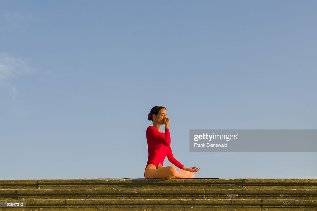 Young woman, wearing a red-orange body suit, is practising... : News Photo
