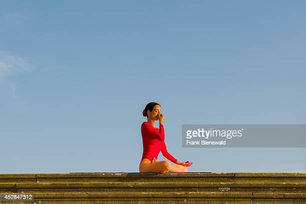 Young woman wearing a redorange body suit is practising HathaYoga outdoor showing the pose anuloma viloma / nadi shodhana pranayama alternate nostril...