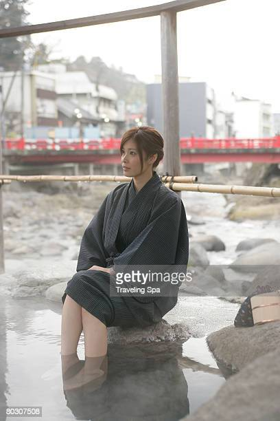 Young woman wearing a robe, soaking in a hot spring