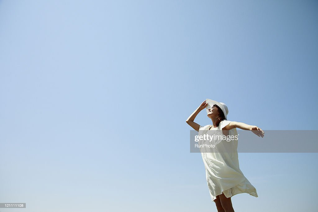 Young woman wearing a straw hat under the sun : Stock Photo