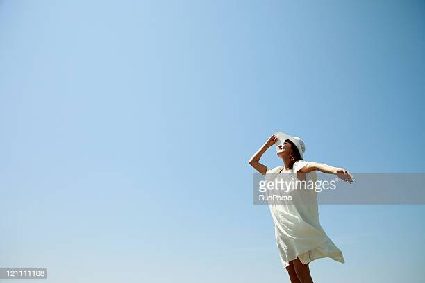 young woman wearing a straw hat under the sun - rafraîchissement photos et images de collection