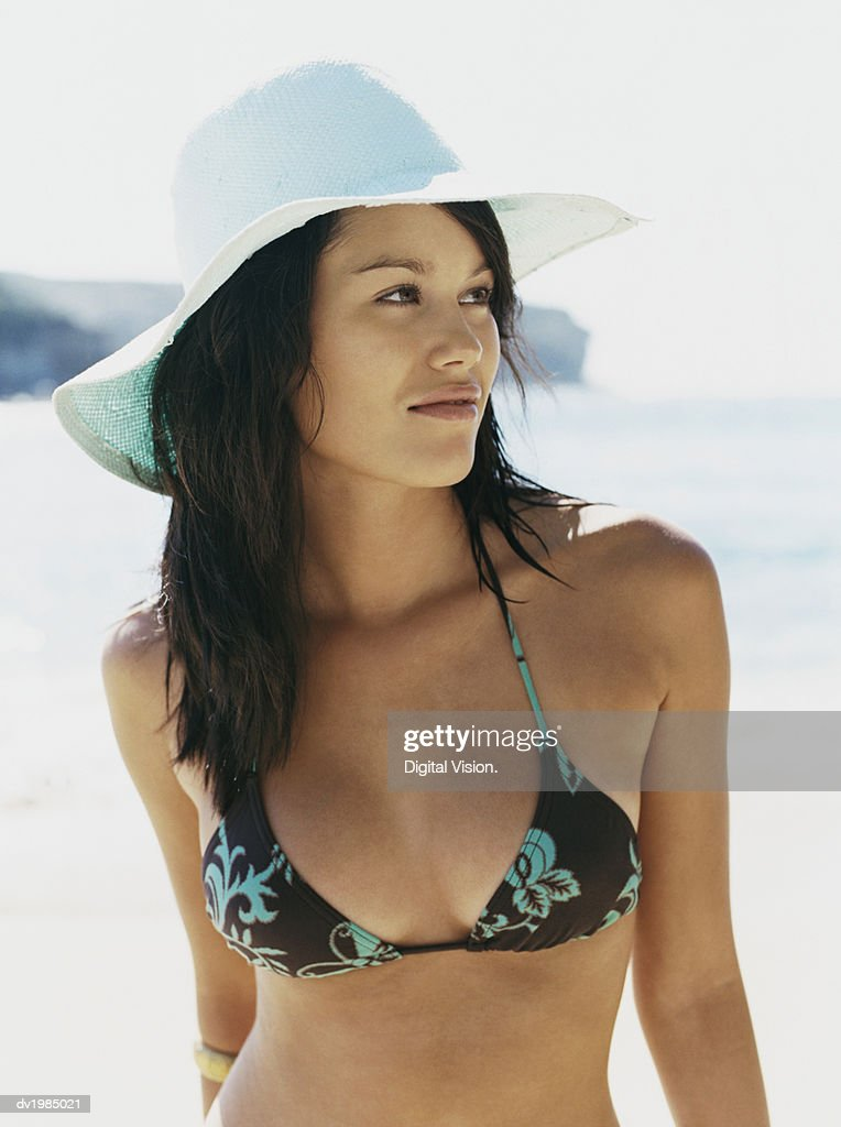 Young Woman Wearing a Sunhat and a Bikini Top Standing by the Sea : Stock Photo