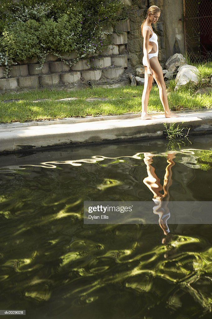 Young Woman Wearing a Swimming Costume and Walking at the Edge of a Lake : Stock Photo