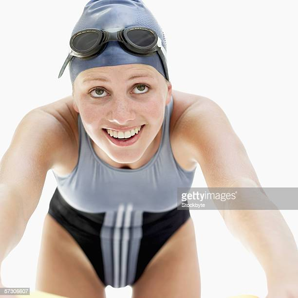Young woman wearing a swimsuit and goggles on her forehead