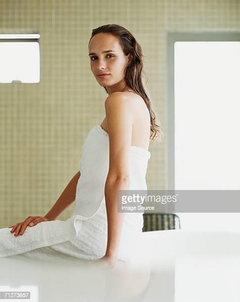 着ている若い女性は、タオルをバスルーム - セミヌード ストックフォトと画像