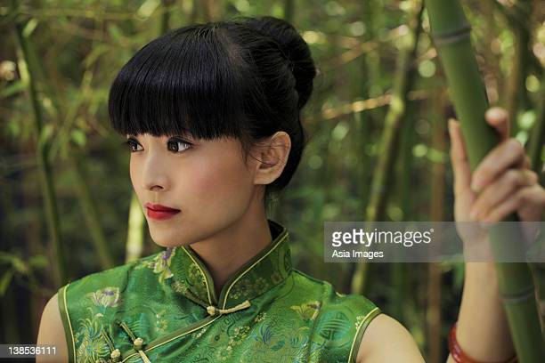Young woman wearing a traditional Chinese dress and standing in front of bamboo trees