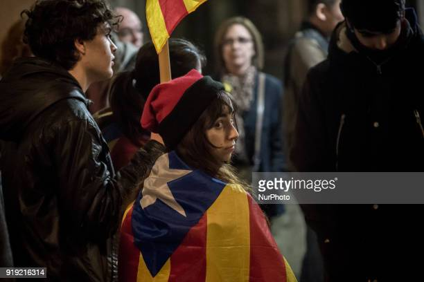 A young woman wearing a traditonal Catalan hat 'barretina' and wrapped with a estelada or proindependence flag looks over during a march in support...