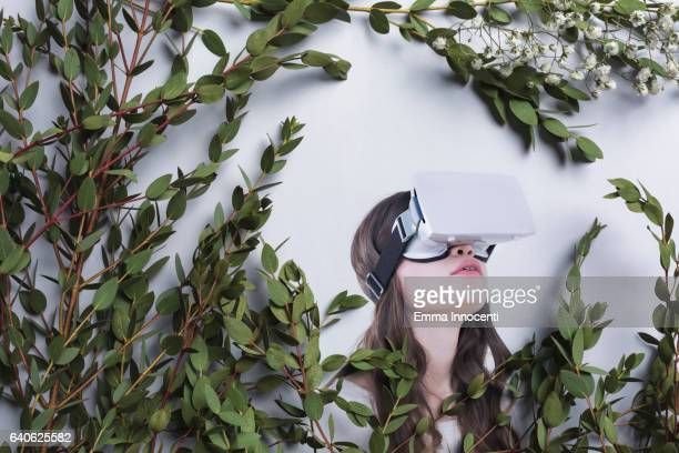 Young woman wearing a virtual reality headset looking up
