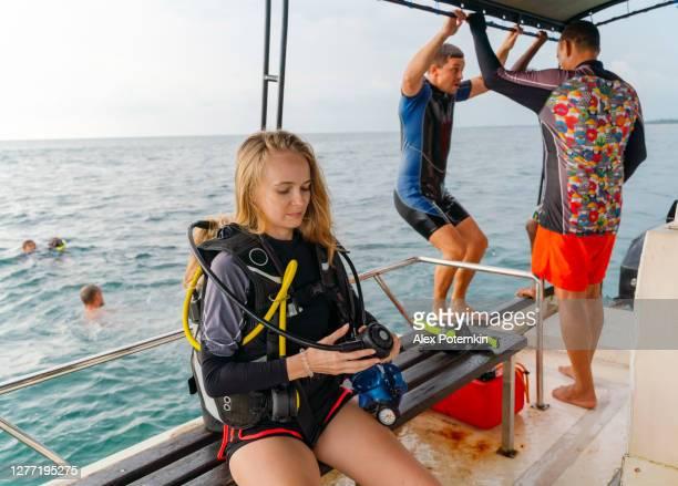 de jonge vrouw die een wetsuit en aqualung draagt wacht op het duiken wanneer de mens voorbereidingen treft om in het overzees van een raad van een boot in de achtergrond te springen. - aqualung diving equipment stockfoto's en -beelden
