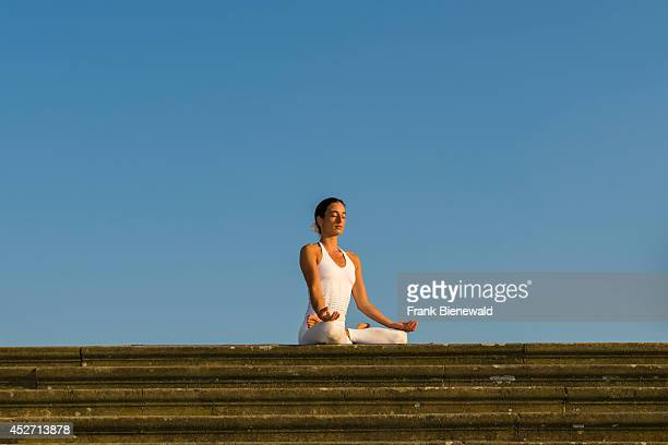 Young woman wearing a white body suit is practising HathaYoga outdoor showing the pose padmasana lotus pose