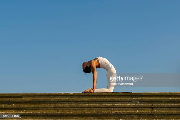 Young woman wearing a white body suit is practising HathaYoga outdoor showing the pose ushtrasana camel pose