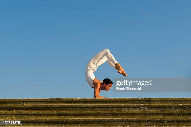 Young woman wearing a white body suit is practising HathaYoga outdoor showing the pose vrischikasana scorpion pose