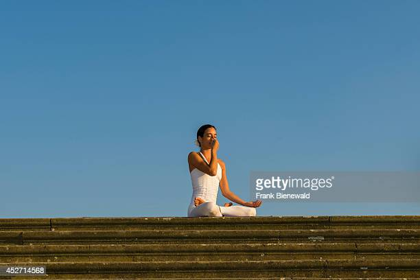 Young woman wearing a white body suit is practising HathaYoga outdoor showing the pose anuloma viloma / nadi shodhana pranayama alternate nostril...
