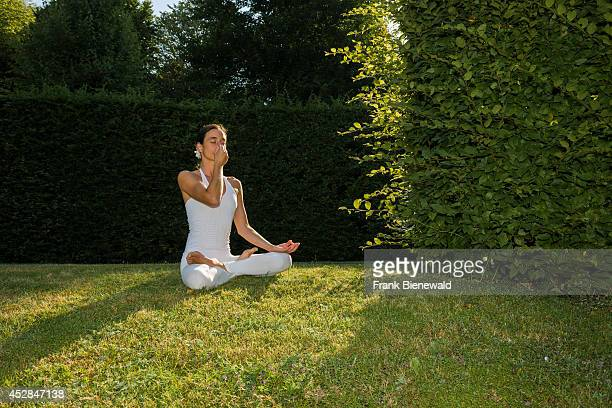 Young woman wearing a white body suit is practising HathaYoga outdoor between trees showing the pose anuloma viloma / nadi shodhana pranayama...