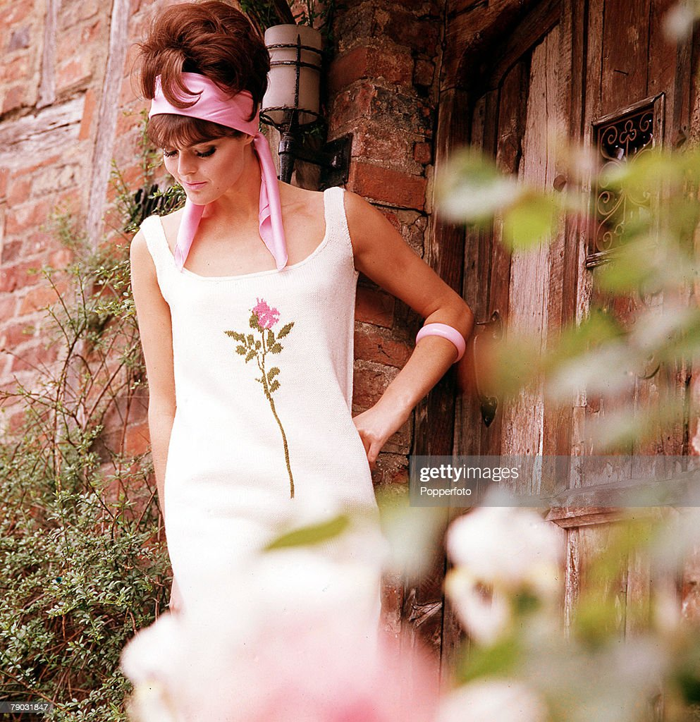 1965 A Young Woman Wearing A White Dress With A Flower Pattern On
