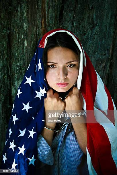 young woman wearing american flag and handcuffs - unfairness stock pictures, royalty-free photos & images