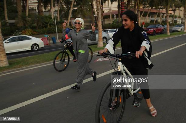 A young woman wearing an abaya designed specifically for sports runs along side two girls on bicycles on the Corniche seafront on June 24 2018 in...