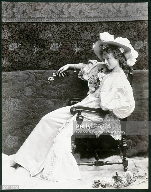 Young woman wearing an elaborate dress and hat sitting in a chair against a back drop holding a rose c 1890s Studio portrait by James Arthur