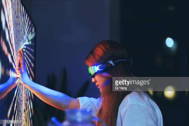 young woman wearing augmented reality glasses touching screen with hands - touching stock pictures, royalty-free photos & images