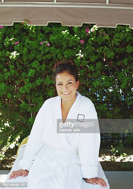 Young woman wearing bathrobe on massage table, smiling, portrait