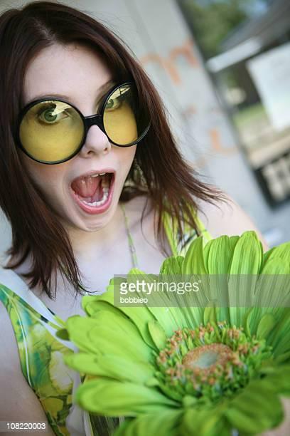 Junge Frau mit großen Sonnenbrille hält großer Blume
