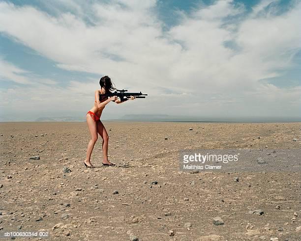 young woman wearing bikini aiming machinegun in desert - machine gun stock pictures, royalty-free photos & images