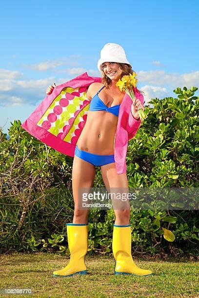 Junge Frau mit Bikini und Regenjacke mit Stiefeln