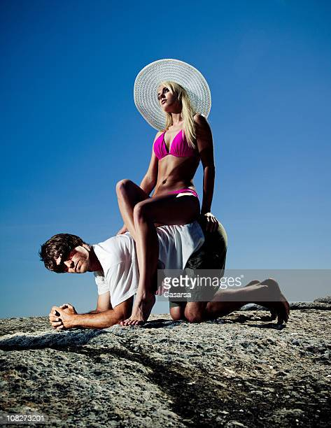 young woman wearing bikini and sitting on man's back - women dominating men stock photos and pictures