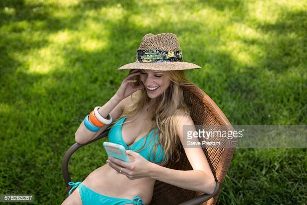 Young woman wearing bikini and sunhat reading smartphone texts in garden