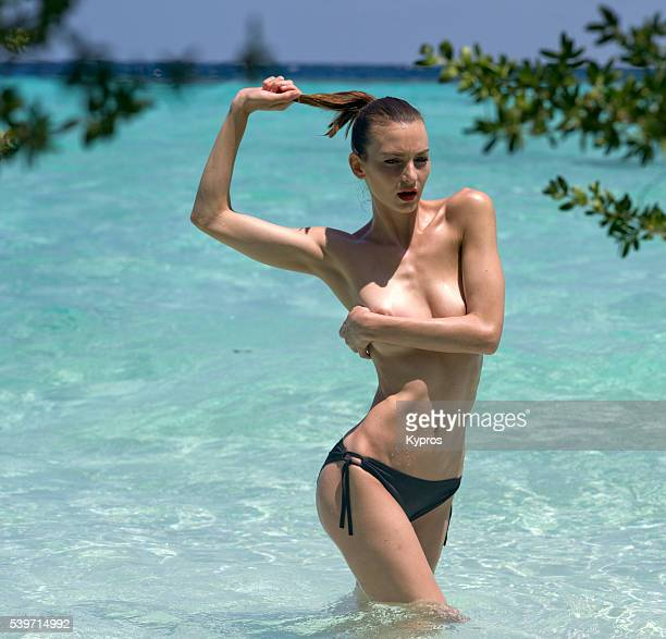 young woman wearing bikini bottoms standing in the indian ocean pulling her hair and covering chest with arms - maldives - chiuso per ferie foto e immagini stock