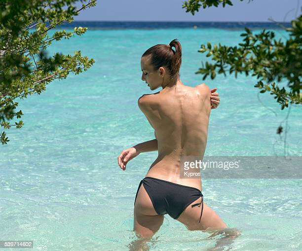 young woman wearing bikini bottoms standing in the indian ocean rerar view - maldives - indian bikini stock pictures, royalty-free photos & images