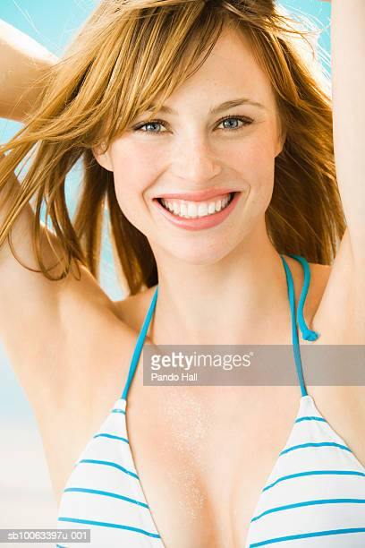 Young woman wearing bikini, hands behind head, smiling, portrait