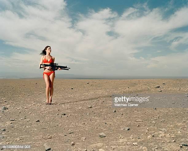young woman wearing bikini holding machinegun in desert - machine gun stock pictures, royalty-free photos & images