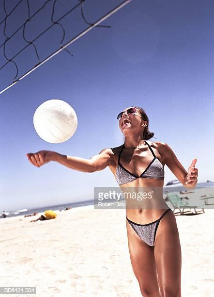 young woman wearing bikini striking volleyball on beach. - damen volleyball stock-fotos und bilder