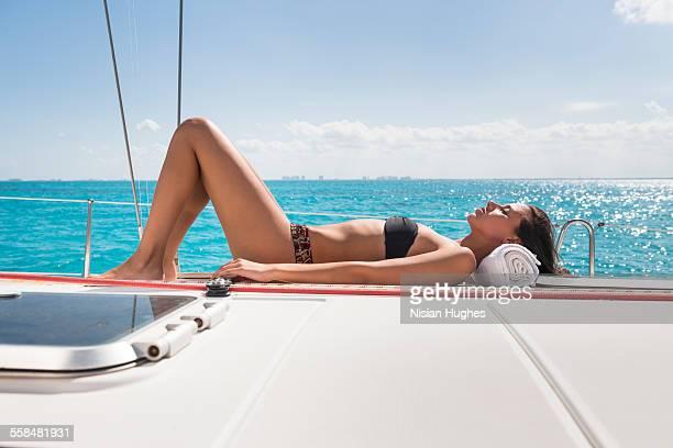 young woman wearing bikini sunbathing on sailboat