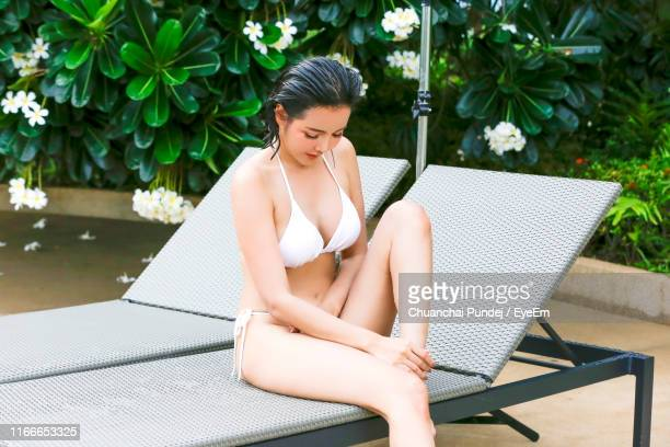 young woman wearing bikini while sitting on lounge chair at poolside - beautiful woman chest stock pictures, royalty-free photos & images