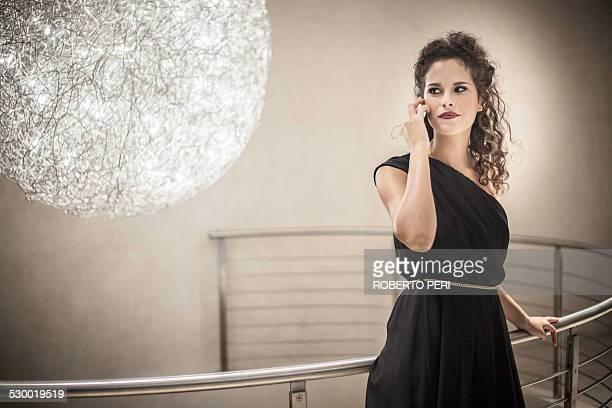 young woman wearing black dress on cell phone, portrait - roberto ricciuti foto e immagini stock