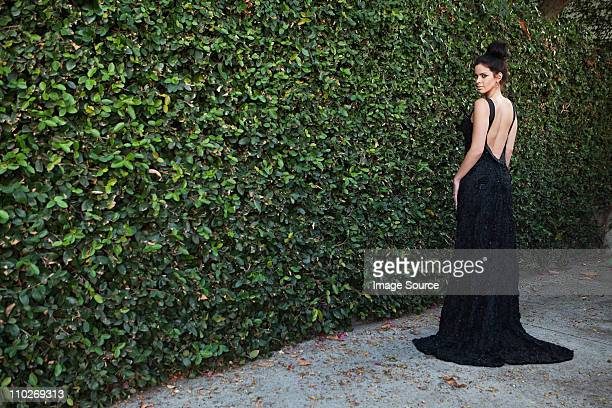 young woman wearing black evening dress, standing by hedge - evening gown stock photos and pictures