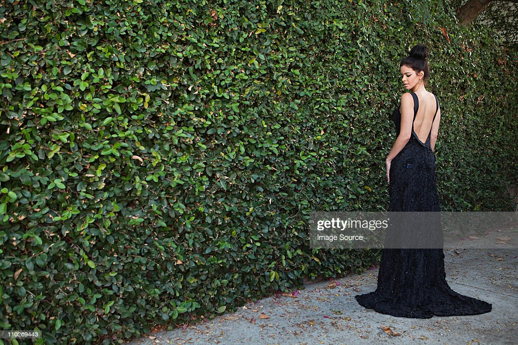 Young woman wearing black evening dress, standing by hedge : Stock Photo