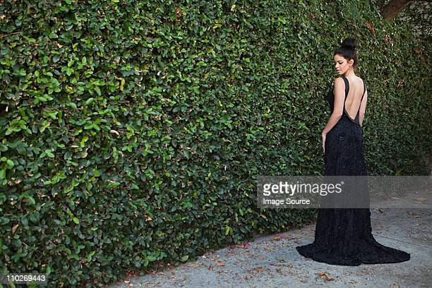 Young woman wearing black evening dress, standing by hedge