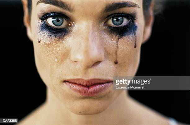 Young woman wearing black eye make-up, crying, close-up