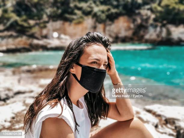 young woman wearing black mask at beach. summer, tourism, virus, corona, covid-19. - bronzage masque photos et images de collection