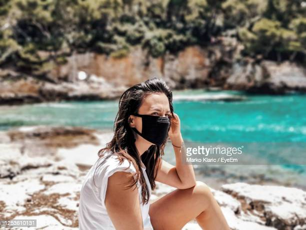 young woman wearing black mask at beach. summer, tourism, virus, corona, covid-19. - scuba mask stock pictures, royalty-free photos & images