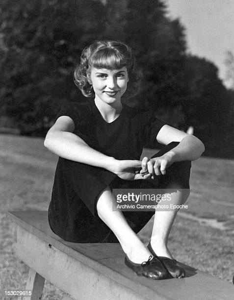 A young woman wearing black trousers and a black shirt portrayed while sitting on a park bench circa 1948