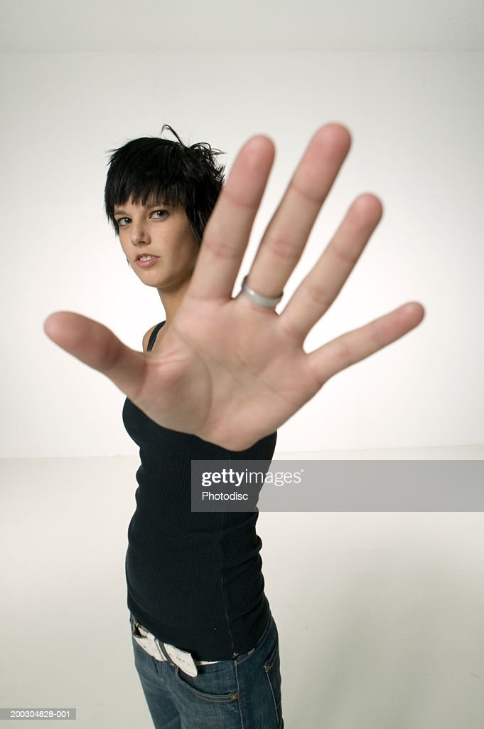 Young woman wearing black vest giving stop signal, posing in studio, portrait : Stock Photo